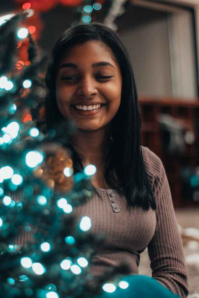selective focus photography of smiling woman beside christmas tree