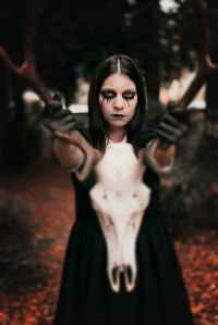 woman in black dress holding animal skull