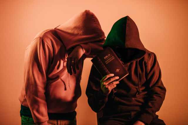 two person in pullover hoodies holding book