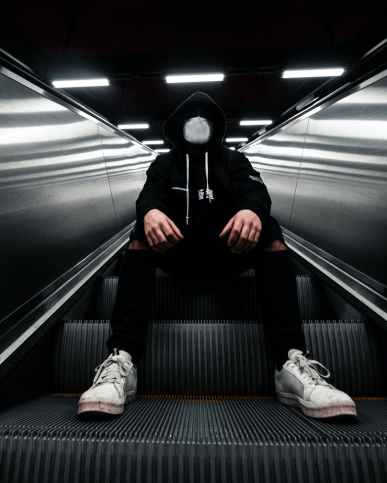 person sitting on escalator